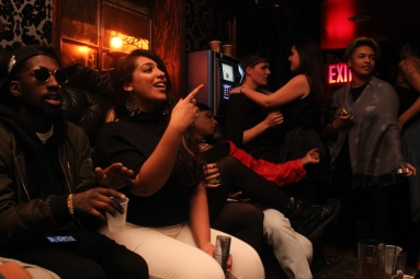 Partygoers hang out on a couch in a bar called The Flat in Brooklyn, NYC 03/08/2014 © Sumi Naidoo, 2014